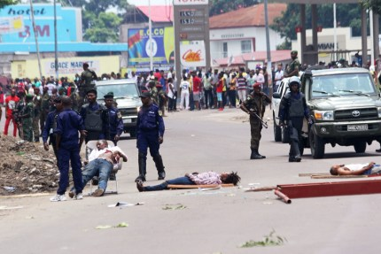 The bodies of people killed during election protests lie in the street as Congolese troops stand nearby in Kinshasa, Democratic Republic of Congo, on Sept. 19. – Photo: John Bompengo, AP