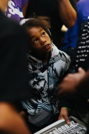 A child looks up at Kaepernick. What an opportunity to spend time with a celebrity who thinks like a Black Panther! – Photo: Katrina Britney Davis, The Undefeated