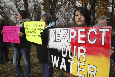 Holly Doll of Mandan, North Dakota, an enrolled member of the Standing Rock Sioux Tribe, holds a protest sign outside the state capitol in Bismarck. – Photo: John L. Mone, AP