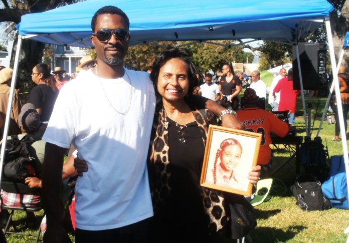 Mercedes-Rodriquez-holds-photo-of-daughter-Ameenah-murdered-1981with-son-Rasheed-at-annual-McClymonds-HS-Reunion-Bobby-Hutton-Park-Oakland-by-Jahahara, Support the Bay View and our righteous movements!, Culture Currents