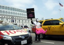 A protester who declined to give his name mocks ap-based ride-selling company Lyft and its signature pink mustaches at a cab driver rally outside San Francisco City Hall on Tuesday, July 30. (Alex Emslie/KQED)