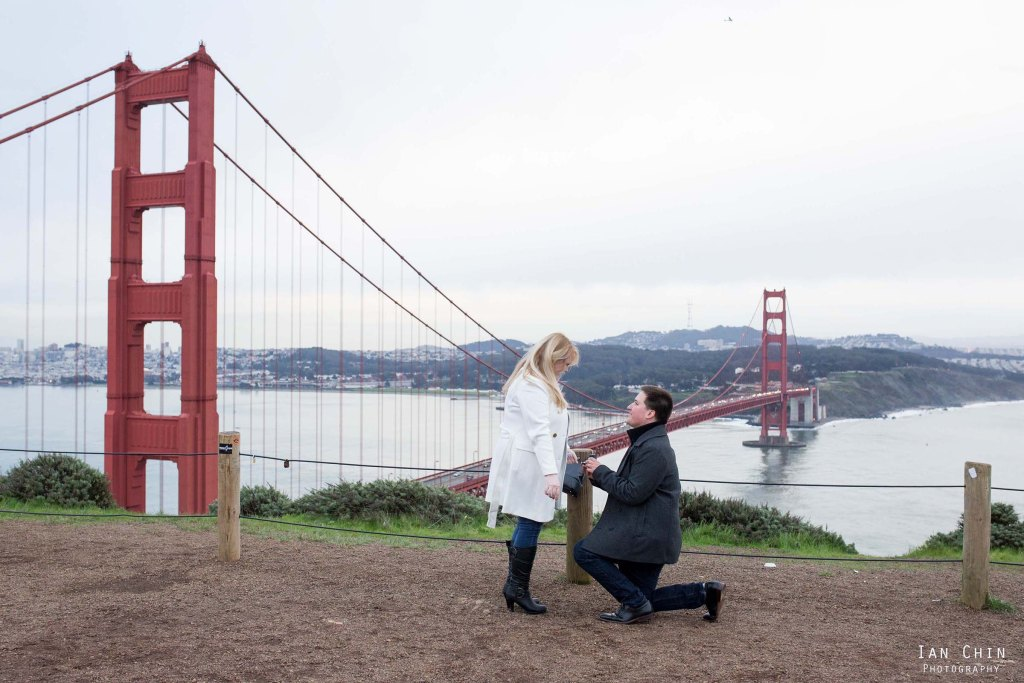 batter spencer marriage proposal on a foggy day with a guy in black on his knee proposing to his girlfriend in white with the golden gate bridge in the background