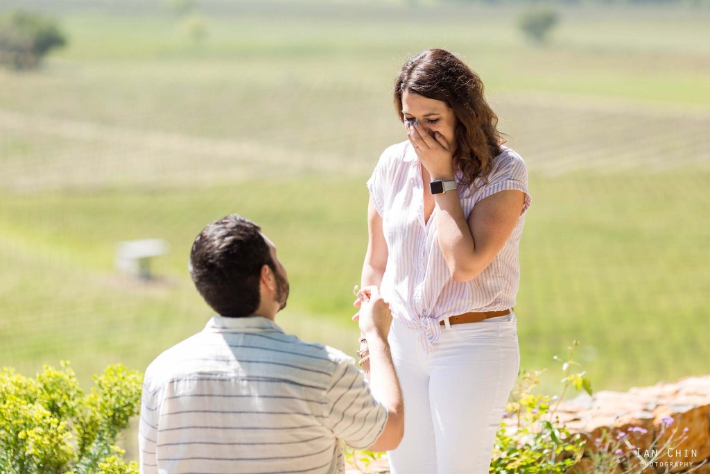 Gargiulo Vineyards marriage proposal in Napa with a guy on his knee holding a ring to a girl covering her mouth in white pants