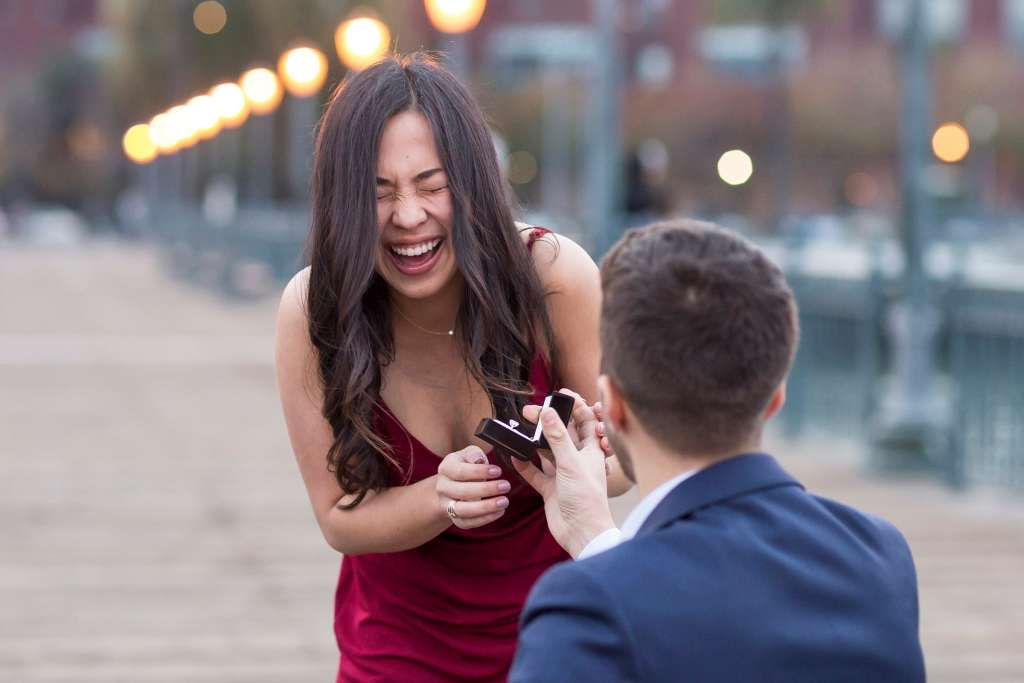 pier 7 marriage proposal with a girl in a red dress shocked as a guy in a blue suit is on his knee proposing with the ring