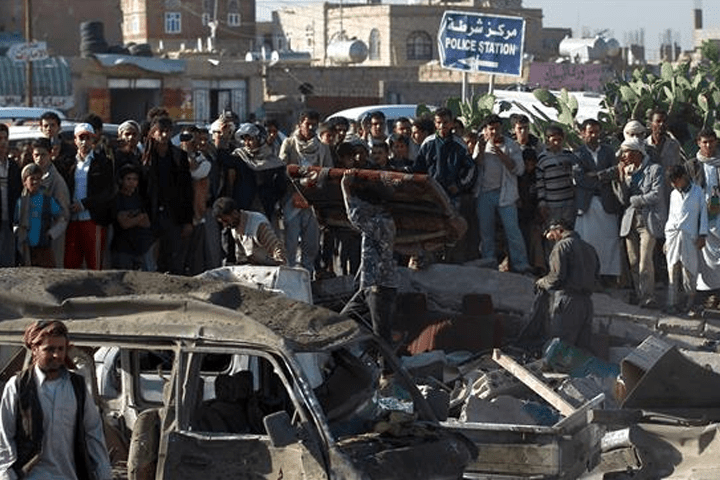 Yemeni civilians and security forces stand at the site of a Saudi air strike near Sana'a Airport on March 26, 2015. © AFP