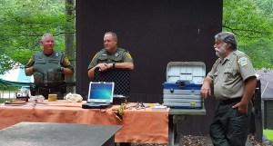 Three forest rangers displaying tracking equipment
