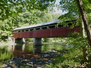 Covered bridge over the Lower Humbert river, red and white about 50 foot long and about 15 feet above the river.