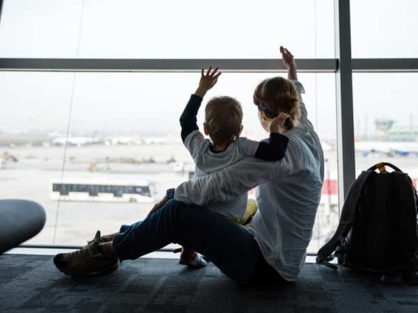 Mom son waving airport window