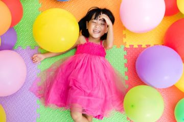 Child lying on a colourful mat laughing in delight