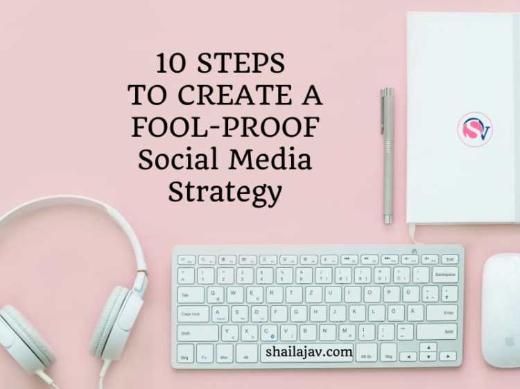 Laptop, headphones, pen and notepad placed on a pink background. Text overlay reads: 10 Steps to create a fool proof social media strategy for your blog or business