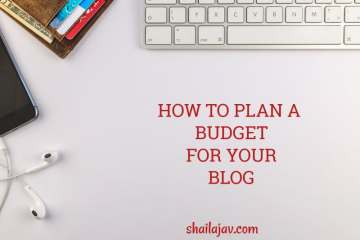 Laptop keys next to a wallet with credit cards and a pair of headphones. How to plan a blog budget and why you should.