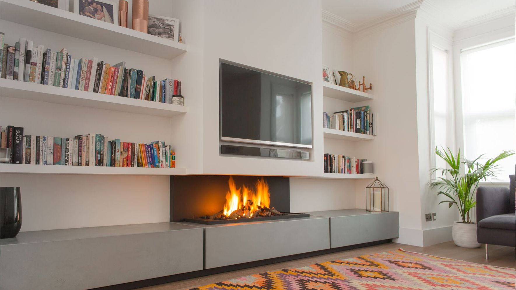 Amazing interior design showing enclosed log burning fireplace along with savvy TV wall Image 7