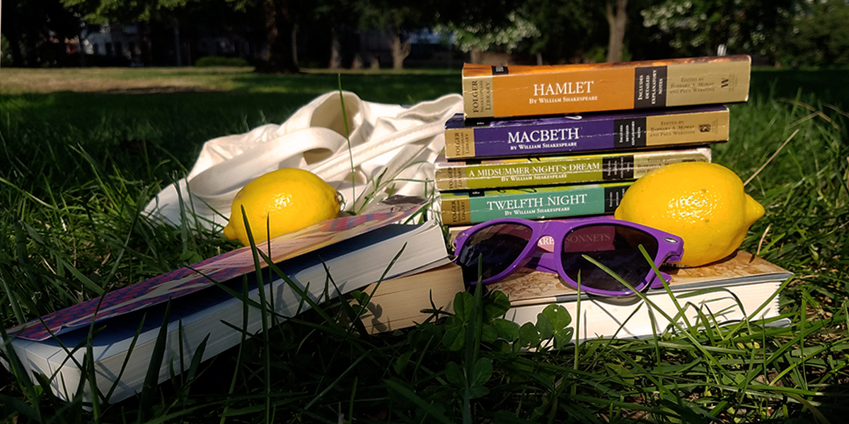 A pile of books sits in the grass under a tree, along with a pair of purple sunglasses and some lemons.