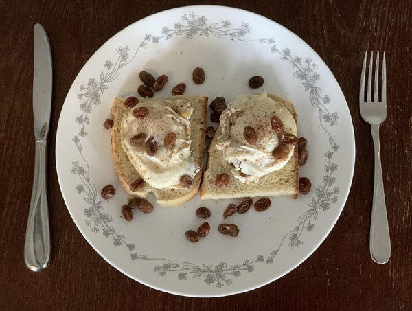 Two poached eggs on toast with raisins on a plate
