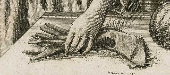 a hand grasping a pair of gloves on a table