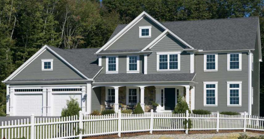 Roofing and siding on a new house with white picket fence