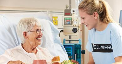 Teenage Volunteer Serving Senior Female Patient Meal In Hospital Bed