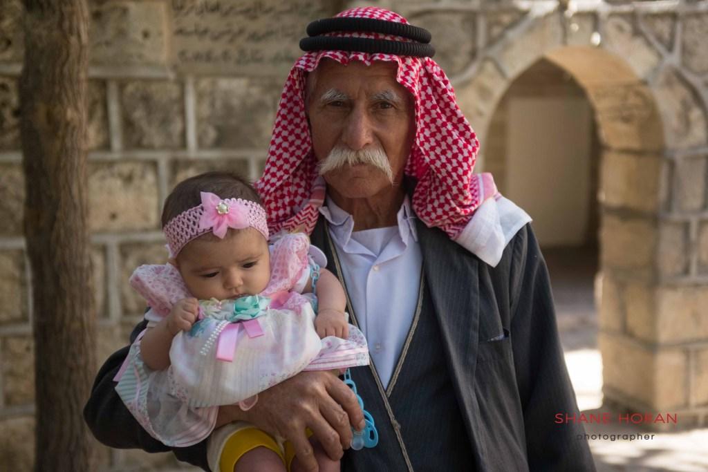 Yazidi man and grandchild at the holy temple of Lalish, Iraq.