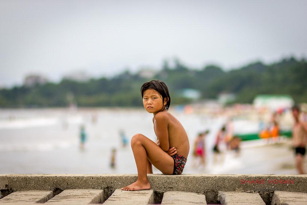 Local child sits on Wonsan Pier, North Korea.