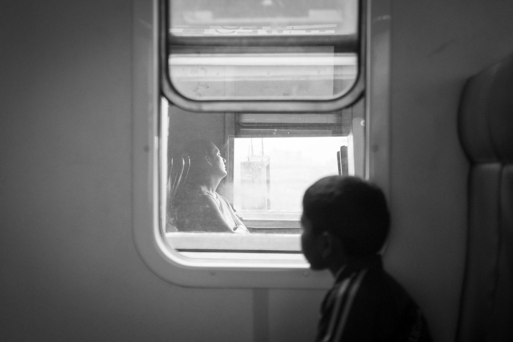 School boy watches a passing train. Sri Lanka