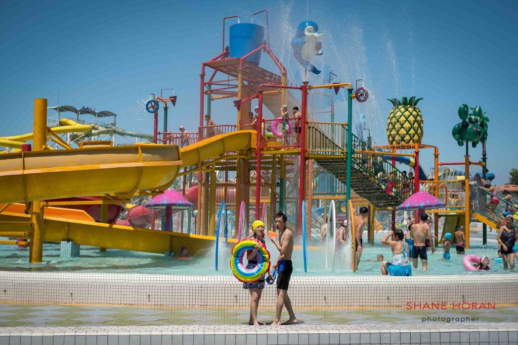 A couple walk around Munsu water park, Pyongyang, North Korea.