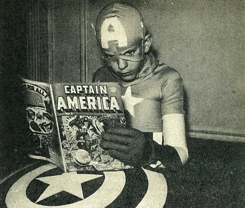 kid in captain america costume reading captain america comic book black and white photo