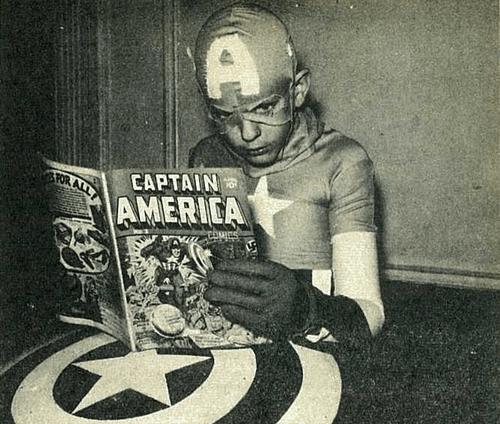 kid in captain america costume reading captain america comic book black and white photo