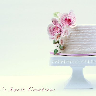 mini ruffled wedding cake with pink sugar orchids