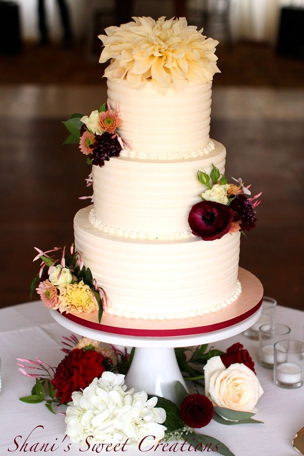 elegant buttercream cake with fresh flowers