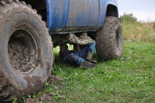 Logan Douglas attempts to take the starter out of an unusable truck to put in his mud bog trunk in Farwell, Mich. on Friday Oct. 4, 2013.