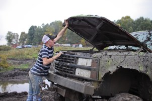 Logan Douglas, age 16, looks under the hood of his truck to try to find out why it won't start in Farwell, Mich. on Friday Oct. 4, 2013.