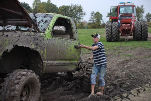 Logan Douglas, age 16, gets into his truck after hooking it up to a tractor to be pull out of a mud pit in Farwell, Mich. on Friday Oct. 4, 2013.