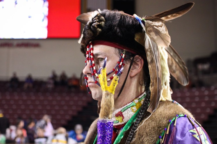 Jefferson Ballew, from Pakagon Band Potawatomi watches dancers competition at the 25th Annual Celebrating Life Pow Wow in McGuirk Arena Sunday, March 23, 2014.