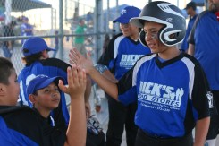Dick's Food Store little league baseball player, Matt Aguayo does a handshake with his teammates before the Semi Final Championship game on the Roy High Field at the Victoria Youth Sports Complex.