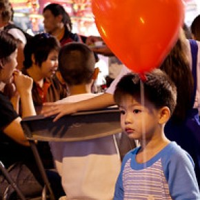 The little boy is rapt with attention on the empty stage at the Chinese New Year festivities in Chiang Mai, Thailand.