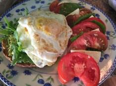 Avocado toast with fried egg and caprese salad
