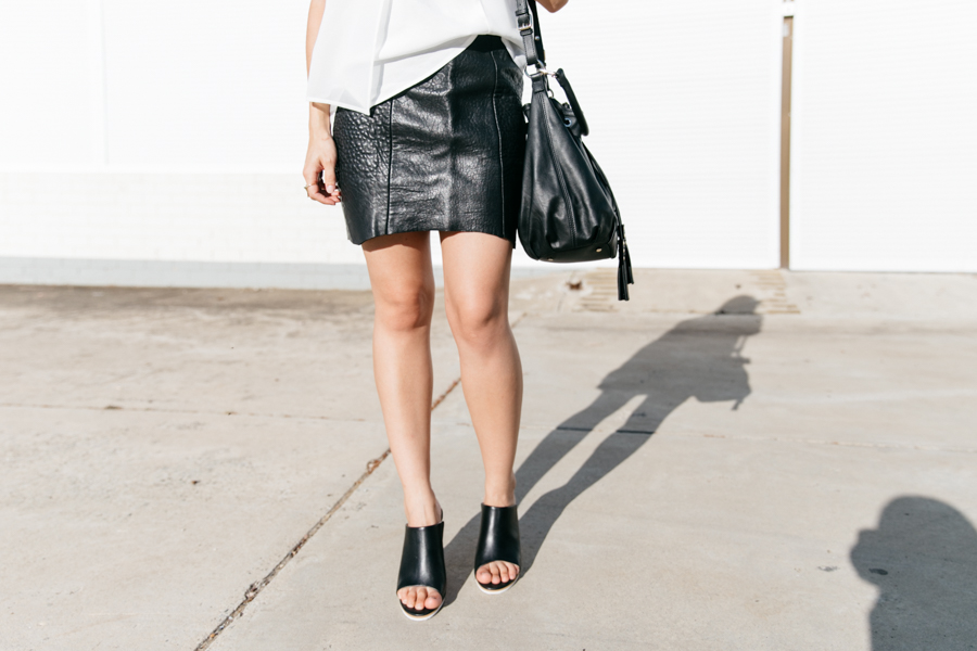 Monochrome minimalist outfit. Black leather skirt with black leather mules & a black leather bag.