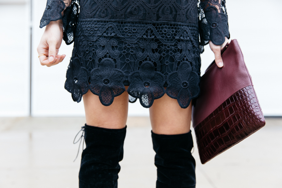 Long sleeve black lace mini dress with knee high boots.
