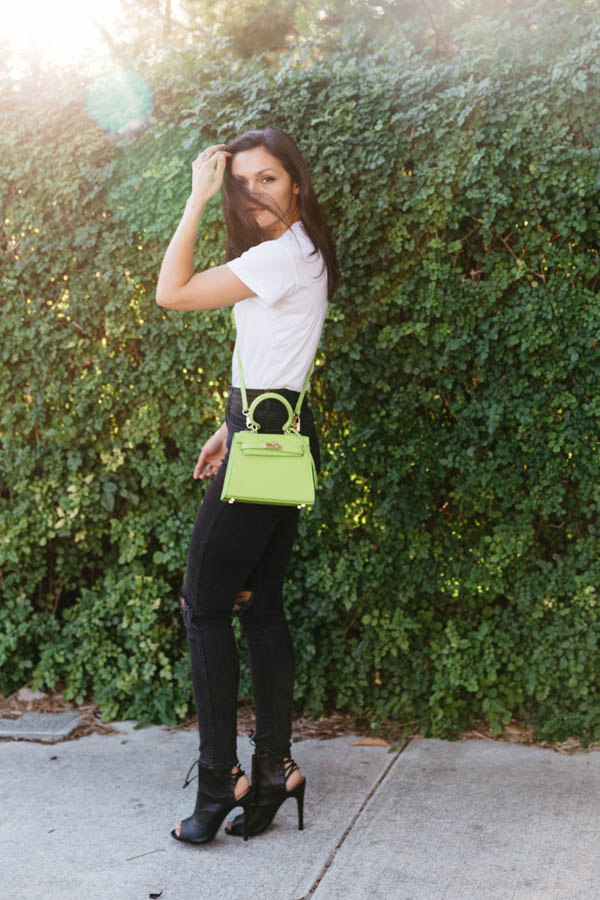 Lime green bag outfit with high waisted black skinny jeans.