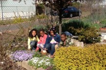 Children posing for a photo in a community garden.