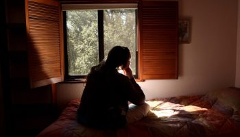 Vista de una mujer sentada en una cama, mirando por una ventana. (© AP Images)