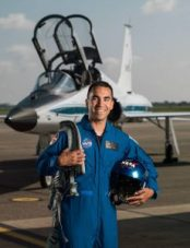 Raja Chari en traje de vuelo delante de un avión (NASA)