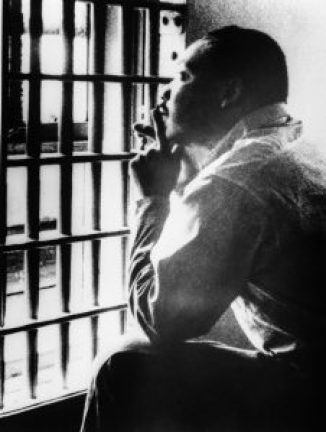 Martin Luther King Jr. mirando por la ventana enrejada de una cárcel (© Bettmann/Getty Images)