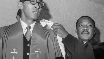 Martin Luther King Jr. coloca una toga religiosa sobre Wyatt Tee Walker (© Bettmann/Getty Images)