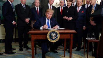 Donald Trump en un escritorio firmando un documento y rodeado de gente (© Evan Vucci/AP Images)