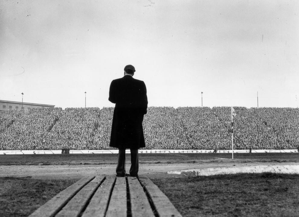 Hombre parado frente a gran multitud de personas en un estadio (© Edward Miller/Getty Images)