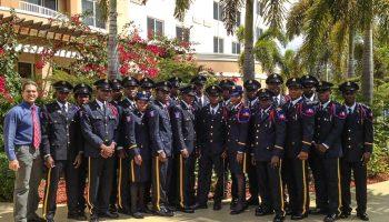 Grupo de personas uniformadas paradas bajo palmeras (© Sargento Oscar D. Pla, Departamento de Policía de Miami-Dade)