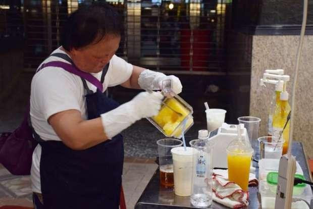 阿美姐負責調飲料、打冰沙,從果汁機舀出新鮮果泥與碎冰調成的清涼,架勢十足(慕哲人社提供)