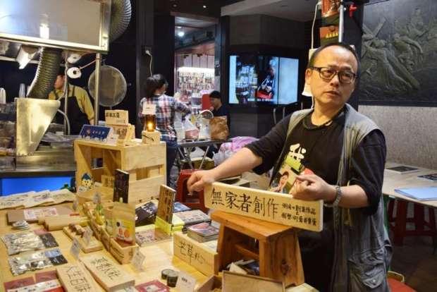 街友藍波擅長木工,顧攤有空時就會磨小木塊鑰匙圈,有客人來就送他(慕哲人社提供)