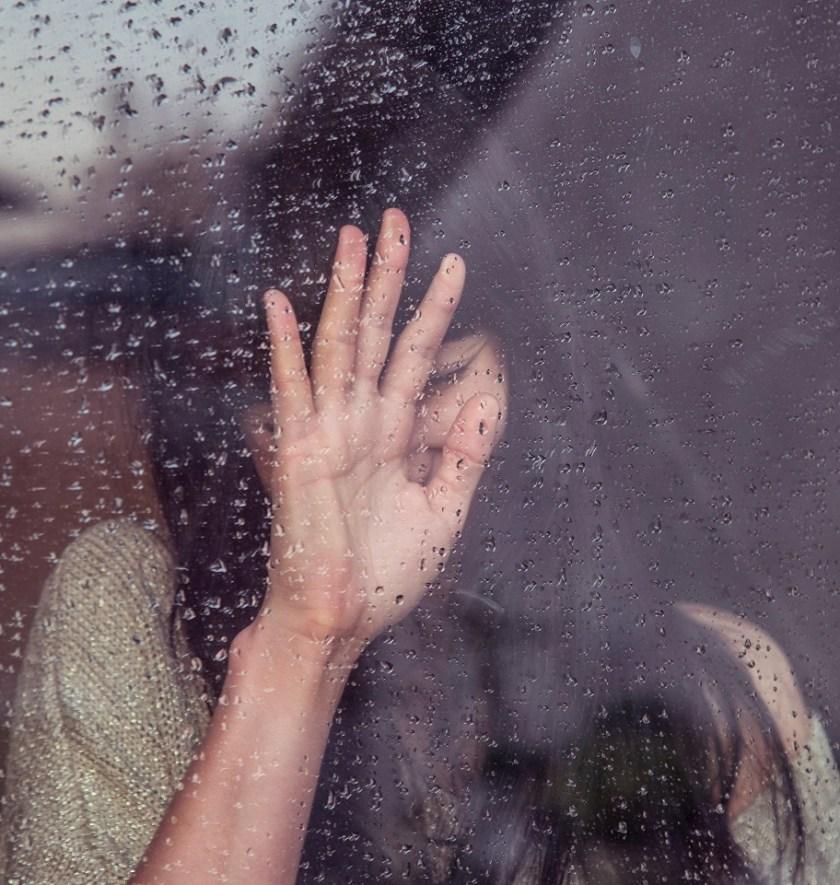 woman raining window
